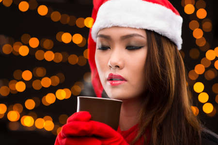 eyesclosed: Close-up image of a young woman in a Santa hat enjoying coffee with cinnamon