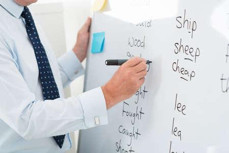Close-up van een mannelijke leraar die Engelse woorden op whiteboard schrijft Stockfoto