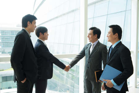foreground: Image of business partners handshaking inside on the foreground  Stock Photo