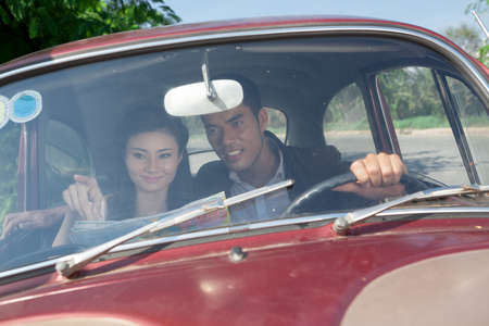 romantics: Young couple sitting in a vintage car and choosing the way