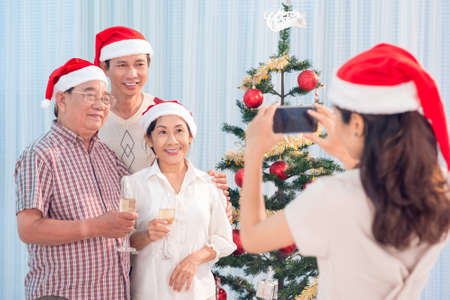 Young woman taking a picture of her family celebrating Christmas