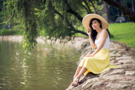 Copy-spaced portrait of a young lady in sombrero hat sitting on the river side  Stock Photo