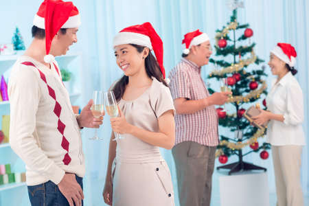 foreground: Festive couple in the foreground clinking glasses to celebrate Christmas