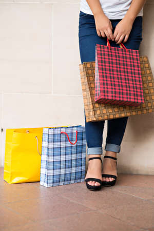 Cropped image of a shopaholic standing and carrying paperbags Stock Photo