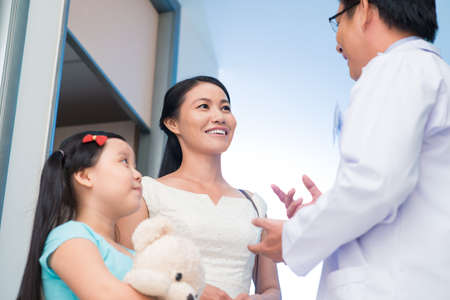 vietnamese: Image of a pediatrician talking with a mom of his little patient viewed below