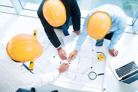 pravítko: Obrázek konstruktérských pracovníků načrtnutých dohromady v popředí, které jsou zobrazeny níže