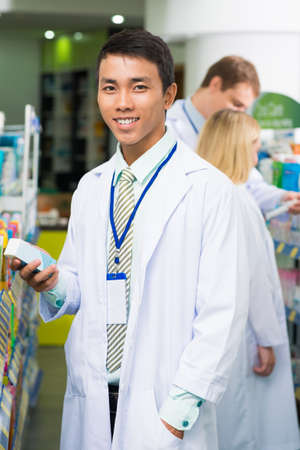 Vertical portrait of a young male pharmacist with a box of treatment standing in the drug-store on the foreground