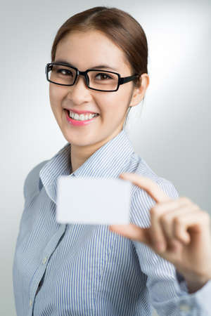 Vertical portrait of a smiling businesswoman giving an id-card on the foreground Stock Photo