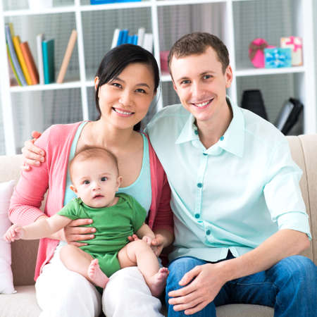 vietnamese: Portrait of a glad young family with a little baby boy posing at camera  Stock Photo