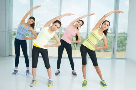 A group of young women warming-up in the aerobics class together