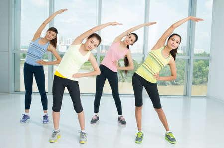 ejercicio aeróbico: Un grupo de mujeres jóvenes Calentamiento en la clase de aeróbic juntos Foto de archivo