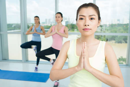 Close-up of a young woman practicing yoga in the aerobics class Stock Photo