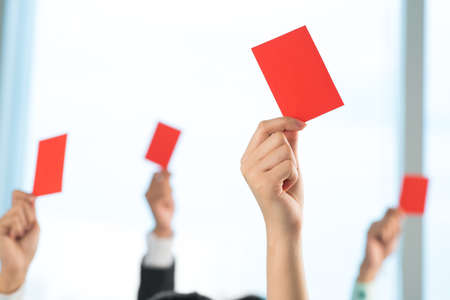 A group of people declined something showing red card on the foreground