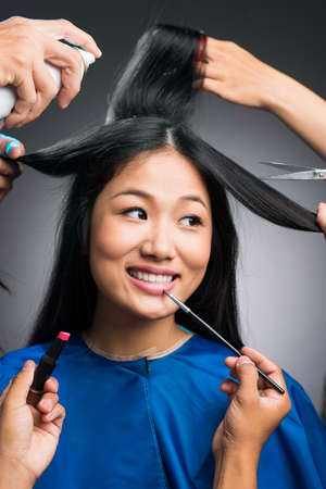 Vertical image of a young woman preparing for something by her professional stylists over grey Stock Photo