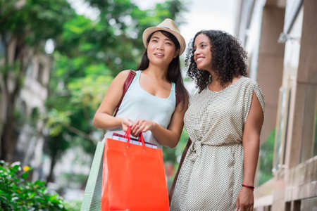 Copy-spaced image of young women having look at the mall with interest on the foreground Stock Photo