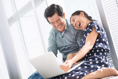 asian family home: Angle view of excited seniors having fun networking at home on the foreground