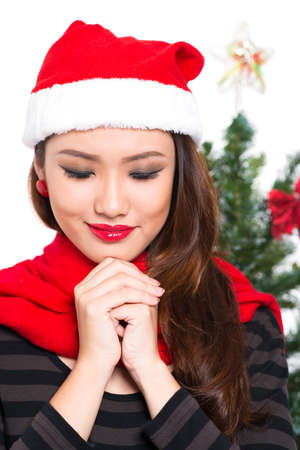 Close-up image of a young beautiful lady making a x-mas wish on the foreground