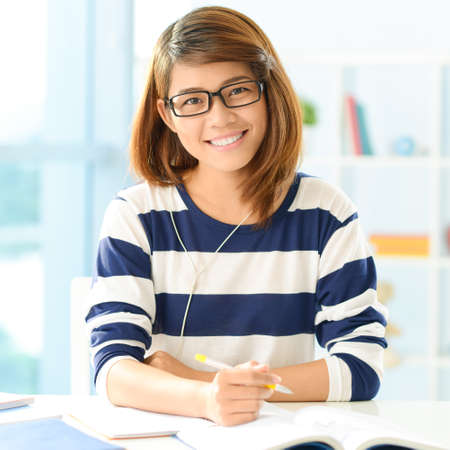 Portrait of an attractive young student doing her homework at home