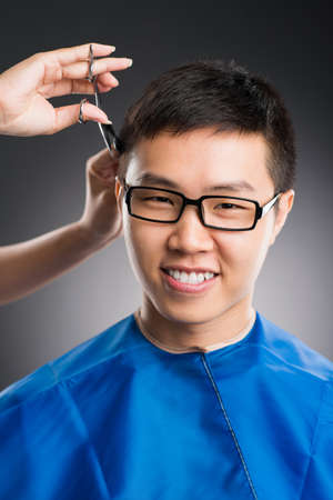 haircutting: Vertical portrait of a young man having haircut over a grey background