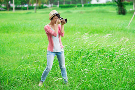 Copy-spaced image of a young female photographer making pictures in the park