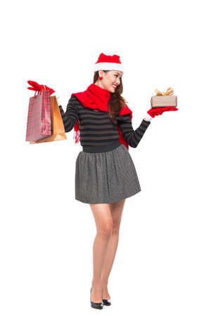Vertical image of a cheerful woman holding shopping bags and a Christmas present in hands over a white background Stock Photo