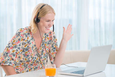 "Copy-spaced image of a young woman showing ""hello"" gesture to somebody talking by Skype on the foreground"
