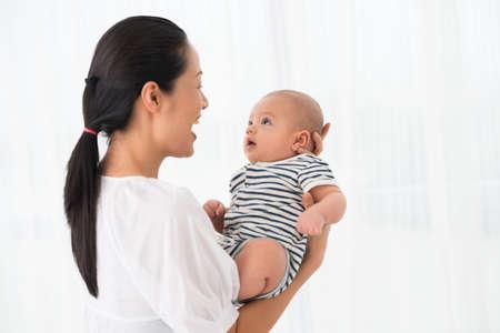 Het exemplaar-uit elkaar geplaatste beeld van een opgewekte moeder die haar zoon houdt overhandigt wit