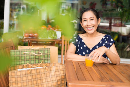 Close-up portrait of an attractive senior lady with shopping bags smiling and looking at camera on the foreground Stock Photo