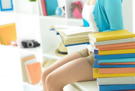 Cropped image of a young girl reading a book at home on the foreground