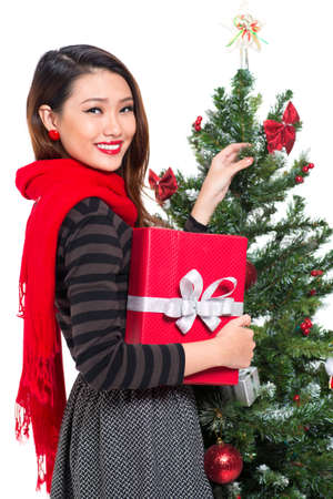 Vertical portrait of a young Christmas girl with a giftbox isolated on white Stock Photo