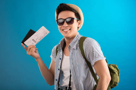 people travelling: Portrait of a cheerful guy with an air ticket in hand smiling and looking at camera isolated on blue