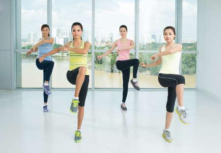 Grupa młodych dziewcząt robi aerobik kroki w klasie sportu