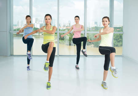 Un grupo de chicas jóvenes que hacen pasos de aeróbic en la clase deportiva