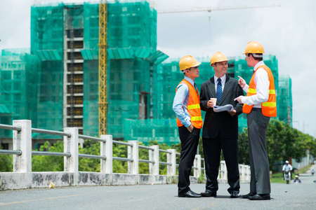 Copy-spaced image of modern engineers discussing something outside Stock Photo