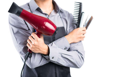 haircutting: Close-up image of a barber with a hairdryer in hand on the foreground Stock Photo