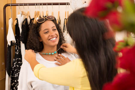 race relations: Image of an attractive lady fitting the necklace in the store on the foreground Stock Photo