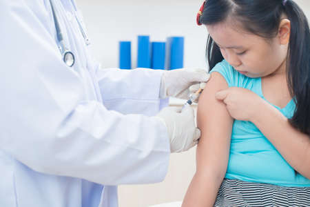 Cropped image of a pediatrician vaccinating his little patient on the foreground