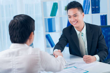 image consultant: Image of a financial consultant shaking hand to his client in the sign of successful cooperation on the foreground