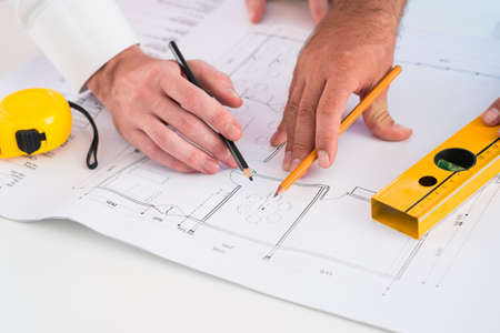 foreground: Cropped image of constructor workers sketching on the foreground Stock Photo