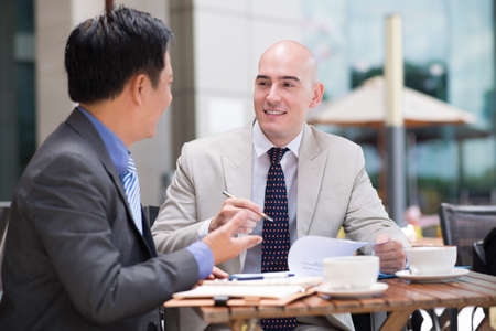 argumentation: Business co-workers dealing together at a cafe on the foreground Stock Photo