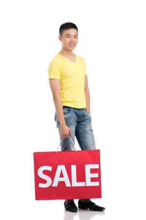 "Full-length portrait of a young man carrying a ""sale"" paperbag over a white background"