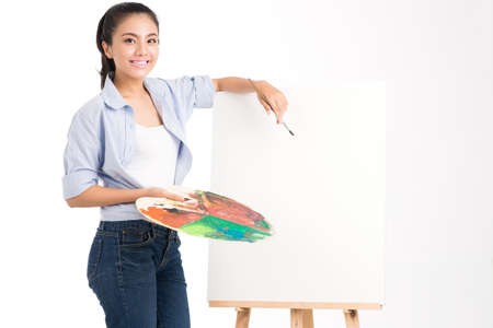 Isolated portrait of an artist standing near the empty canvas ready to draw Stock Photo