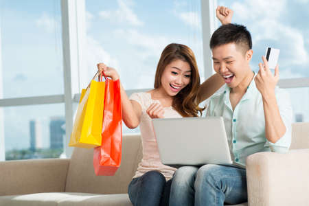 shoppingbag: A young excited couple buying something using Internet at home