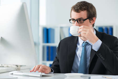 A young businessman drinking a morning coffee at his workplace and typing on the foreground Stock Photo