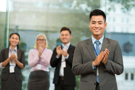 ovation: Portrait of a cheerful applauding businessman on the foreground Stock Photo