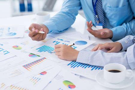 Image recadrée de gens d'affaires discutant de la stratégie d'entreprise sur le premier plan