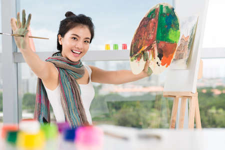 Portrait of a cheerful young artist posing at camera on the foreground