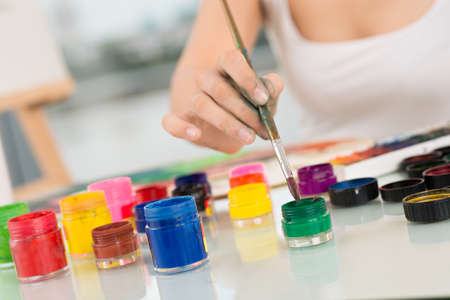 Close-up of a human hand choosing a gouache color on the foreground Stock Photo
