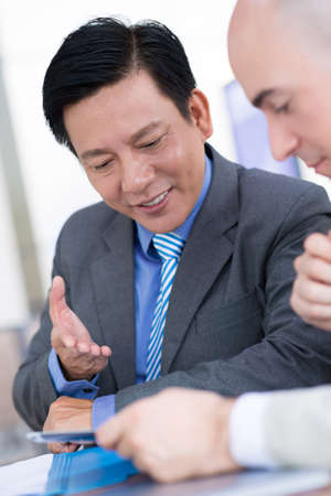 Vertical image of an Asian businessman asking his colleagues about the suggested strategy on the foreground
