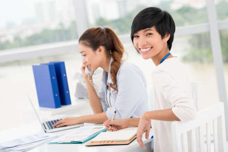 woman work: Portrait of a cheerful businesswoman making notes while her colleagues talking by the phone on the foreground Stock Photo